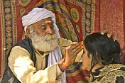 Elderly Holy Man In White Turban Applies Sacred Mark To Pilgrim Woman