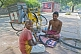 Image of A bicycle repairman fixes a puncture for his customer on the pavement.