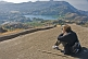 Image of A tourist takes a photograph of Nakki Lake and Mount Abu town.