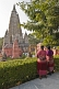 Image of Two Tibetan lady pilgrims rest from their devotions to look at the Mahabodhi Temple.