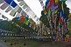 Image of Buddhist monks rest under the shade of trees and prayer-flags.