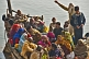 Image of Pilgrims crowd on to a boat to cross the Ganges River.