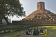 Image of A group of students study in front of the 5thC Chaukhandi Stupa at Sarnath, which has an octagonal tower on top, built by Akbar in 1588.