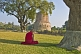 Image of Buddhist monk sits in silent meditation before the 5thC Dhamekh Stupa at Sarnath.