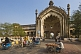 Image of Cycle rickshaws drive through the elaborate gateway of the Rumi Darwaza.