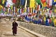 Image of Young trainee Buddhist monk walks past colorful prayer flags.