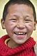 Image of Smiling Buddhist monk in red jersey.