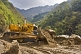 Image of An Indian Army bulldozer deals with a sudden landslide that is blocking a mountain road.