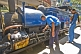 Image of A passenger watches the engineer make adjustments to a steam locomotive on the Darjeeling Himalayan Railway.