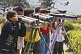Image of Indian tourists view the mountains through home made binoculars at the Batasia Loop.
