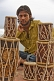 Image of A young Indian man selling drums.