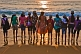 Image of Indian schoolgirls and their teacher line up at the shore to watch the sunset.
