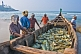 Image of Fishermen with day's catch stored in boat on beach.
