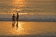 Young Indian couple hold hands in the surf at sunset.