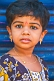 Small Indian girl in gold necklace and earings.