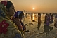 Image of Women pilgrims watch sunrise over ritual bathing area in Ganges Yamuna rivers.