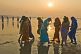 Image of Women pilgrims in saris walk through muddy shallows to get to Ganges river bathing area.