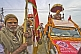 Image of Hindu man holds flag for decorated Sadhu Truck in Kumbh Mela  parade.