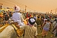 Image of Hindu holy man is supported on horseback through dense  Kumbh Mela crowds.