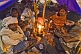 Image of Four Hindu pilgrims huddle around campfire in tent whilst waiting for dawn at Kumbh Mela.