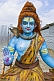 Blue face and torso of clay statue of god Shiva at Kumbh Mela religious festival.