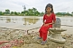 Girl In Red Kurta Sits On Shiva Lingam, With Shiva Statue In Background