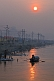 Solitary rowing boat passes bathing pilgrims on River Ganges in early dawn light.