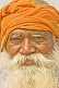 Image of Smiling elderly Hindu Holy Man with orange turban and flowing white beard at Kumbh Mela.