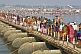 Image of Long lines of Indian Hindu pilgrims cross pontoon bridge over Ganges river.