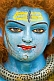 Cracked blue face of clay statue of god Shiva at Kumbh Mela Hindu religious festival.