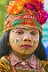 Image of Girl with face paint and flower filled turban raises money from Kumbh Mela pilgrim visitors.