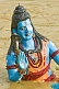 Statue Of Blue-Skinned God Shiva Beckons From The Muddy Waters Of The Ganges