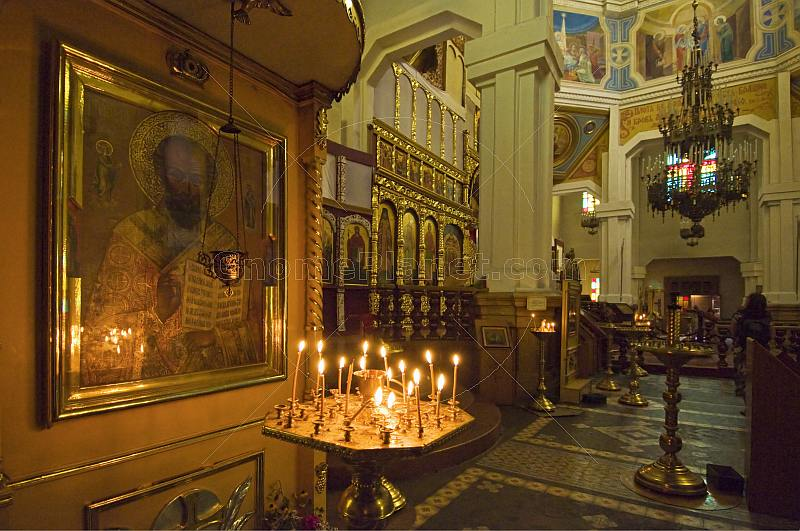 Candle light illuminates an ancient gilded icon in the Zenkov Cathedral.