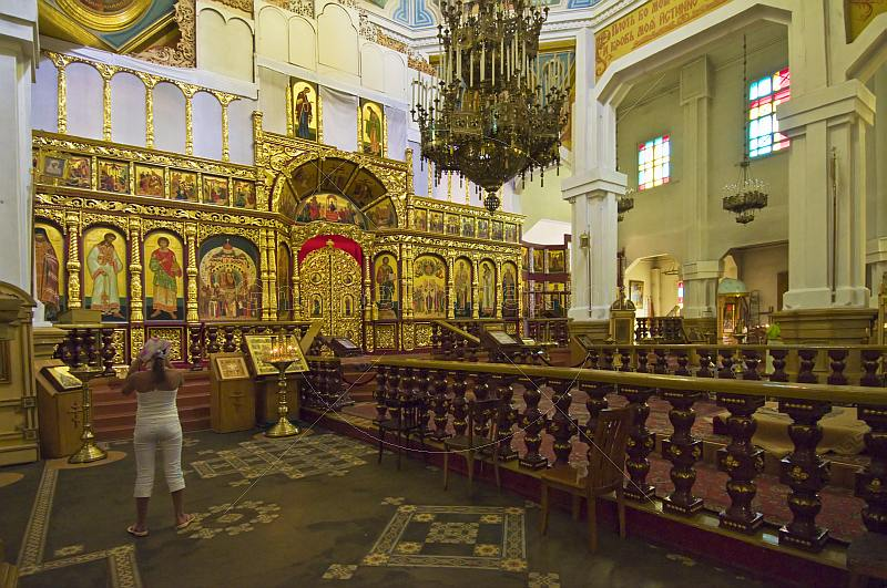 A young girl takes a photograph of icons in the Zenkov Cathedral.
