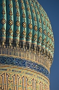Blue tiled dome of the Yasaui Mausoleum in the evening sunlight.