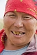 Image of Kazakh woman with red headscarf and gold teeth.