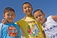 Image of Three Kazakh boys pose for a photo in bright sunshine near the Aral sea.