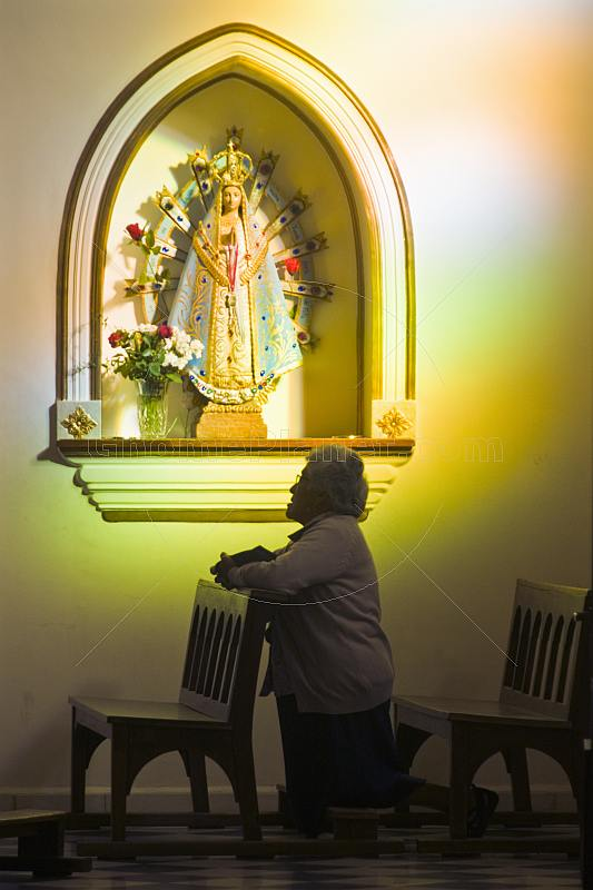 Old woman prays in a side chapel of the Cafayate Cathedral.
