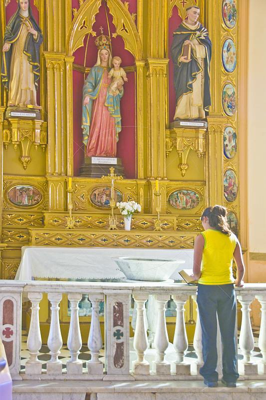 Young woman reads the Bible in the Cafayate Cathedral.