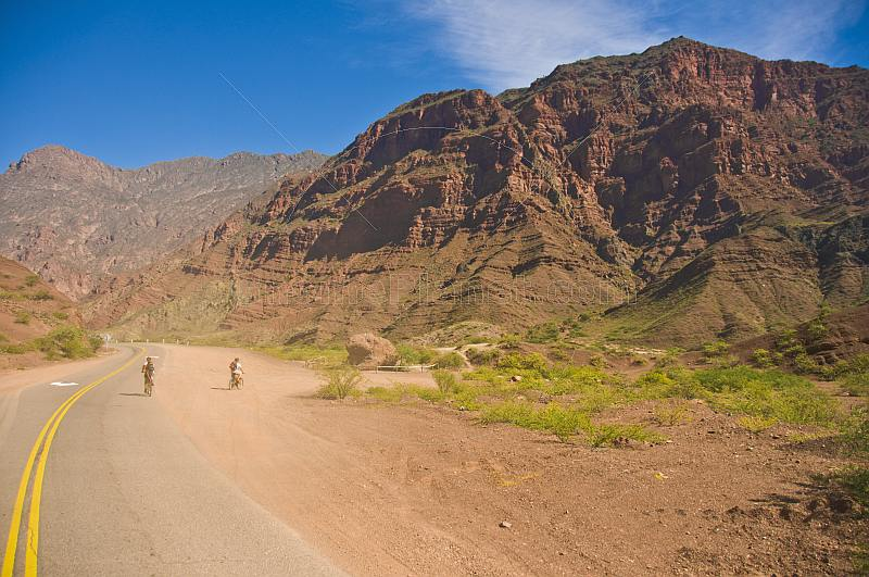 Cyclists admire the mountain scenery of the Quebrada de las Conchas.
