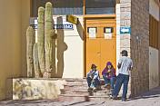 Local people sit outside the main Post Office with large cactus.
