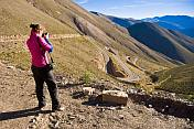 Woman photographs the Cuesta de Lipan - a section of steep zigzag road on the National Route 52 highway.