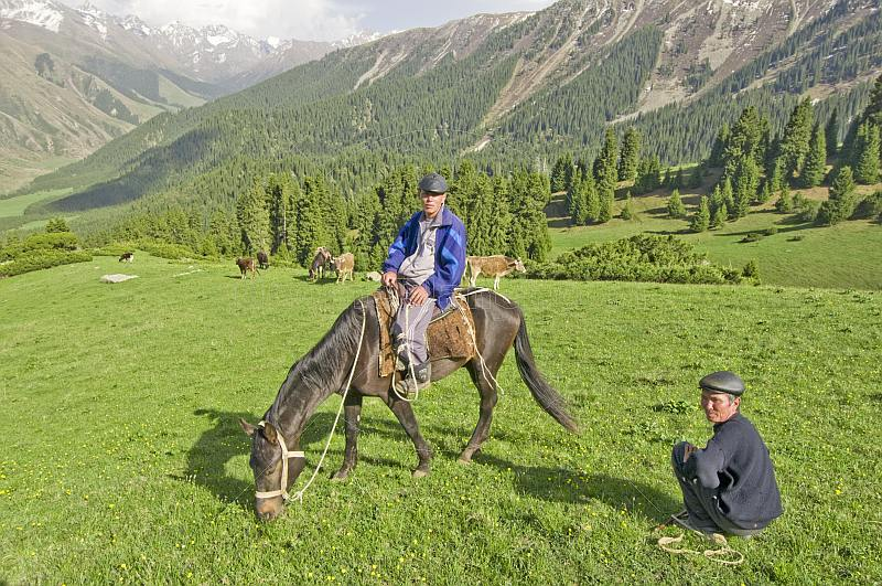 A Kyrgyz Horseman waits with his farmer friend as his horse crops the grass of the Altyn Arashan Mountains.