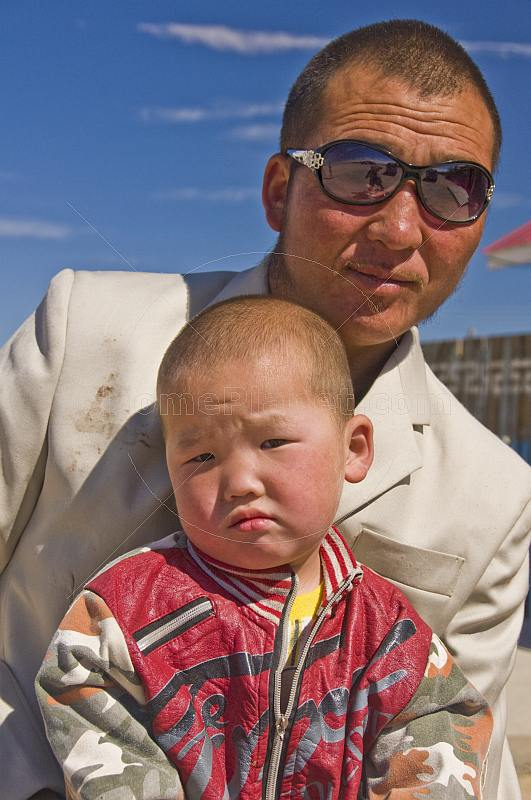 Mongolian shopkeeper and his son, photographed on a motorbike.