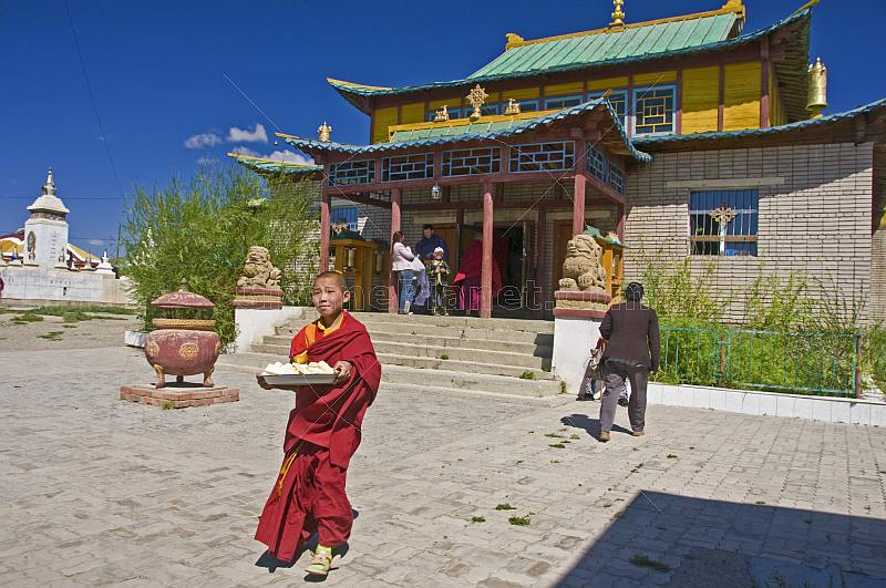 A Buddhist monk carries food to a service in the Gandan Muntsaglan Khiid monastery.
