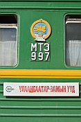 caption: Green railway carriage and destination board for the Ulaan Baatar - Zamyn Uud train.