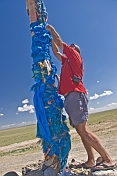 Tying a Blue Khadag scarf to an Ovoo, a Mongolian Shamanistic cairn for travellers.