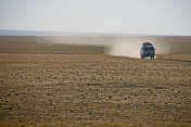 Mongolian minibus raising a dust cloud as it crosses the arid Gobi desert landscape.