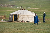 Mongolian man and boy stand next to their yurt.