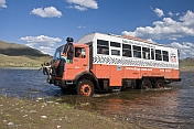 A Dragoman Overland truck fords through a river.